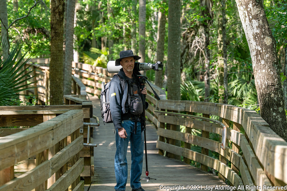 A man with a camera and long lens on the boardwalk at Blue Springs State Park in Florida. Image taken by Joy Aldridge with a NIKON Z 6_2 and NIKKOR Z 70-200mm f/2.8 VR S Z TC-2.0x at 140mm, ISO 500, f5.6, 1/320.