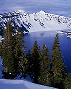The Watchman and Hillman Peak rising above the snowy western rim of Crater Lake, Crater Lake Natonal Park, Oregon.