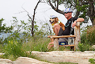 Bear Mountain, New York - A man and his dog, both wearing hats and sunglasses, enjoy the view from the top of Bear Mountain on June 5, 2010.
