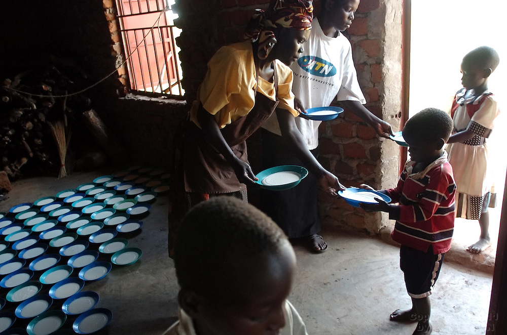 Children recieve bowls of porridge for lunch while in day care at Coope Camp in Gulu District, north Uganda, on October 6, 2006. Coope Camp, with a population of approximately 18,000, is one of 76 camps outside the town of Gulu created for internally displaced people in north Uganda. Since the war began in 1987  over 2 million people have moved from their village homes to camps close to the town of Gulu where they can be protected from the LRA, the Lord's Resistance Army, by the UPDF, the Ugandan People's Defense Force. Over the years the LRA are said to have abducted more than 30,000 children for use as soldiers in their army. The children were often tortured and girls were frequently used as sex slaves. Current peace talks between the Ugandan government and the LRA taking place in Juba, southern Sudan, have the north Ugandan community hoping for an end to the 20 year long war..Photo by Erin Lubin