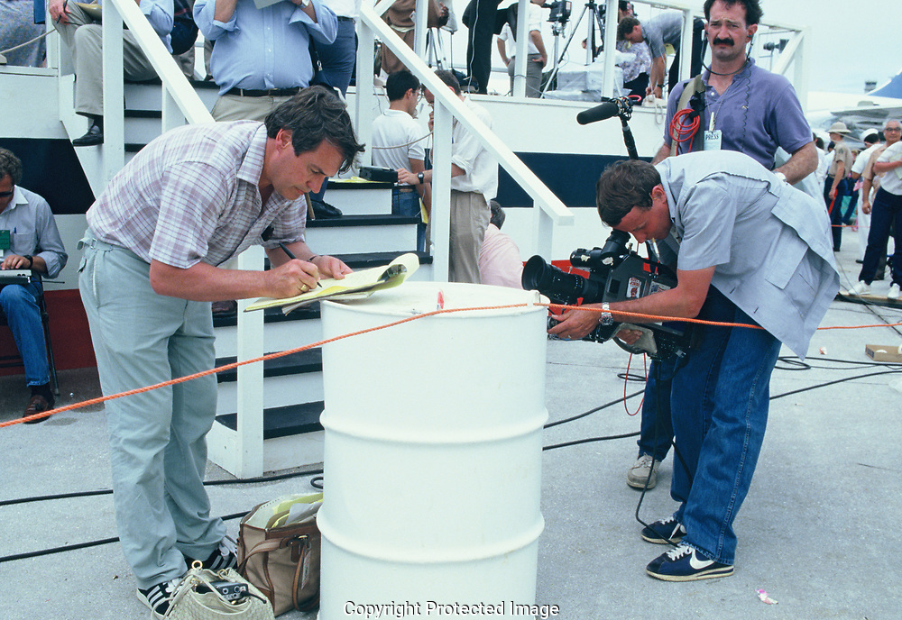 CBS cameraman Mike Marriott and sound man Dan Radovsky photograph an Australian Journalist who may have been removed from the press plane when  President Reagan arrived in Indonesia<br />Photo by Dennis Brack