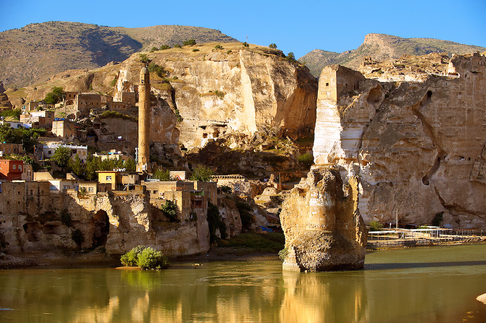 Remains of medieval Artukid Old Tigris Bridge – Built in 1116 by Artukid Fahrettin Karaaslan, the biggest in Anatolia at the time, with the old town Hasankeyf and its ruins on the cliffs abover the river Tigris. The minaret is of the El Rizk Mosque built 1409.  Turkey. 8 .<br /> <br /> If you prefer to buy from our ALAMY PHOTO LIBRARY  Collection visit : https://www.alamy.com/portfolio/paul-williams-funkystock/hasankeyf-turkey.html<br /> <br /> Visit our PHOTO COLLECTIONS OF TURKEY HISTOIC PLACES for more photos to download or buy as wall art prints https://funkystock.photoshelter.com/gallery-collection/Pictures-of-Turkey-Turkey-Photos-Images-Fotos/C0000U.hJWkZxAbg