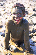 A073TP Child smiling playing in thick mud with body covered by brown mud