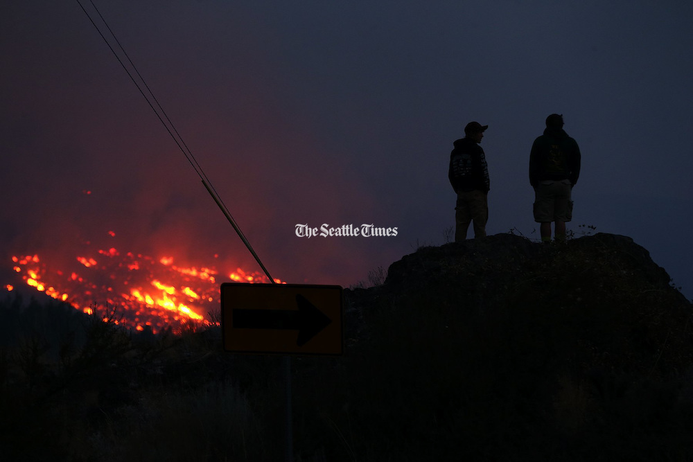 Two men from Twisp watch fires burn from above the town early in the morning Thursday, Aug. 20, 2015.<br /> <br /> Erika Schultz / The Seattle Times