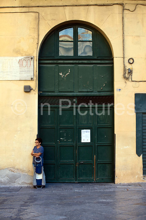 A woman stands with her shopping trolley in Paizza Bellini, Palermo, Italy