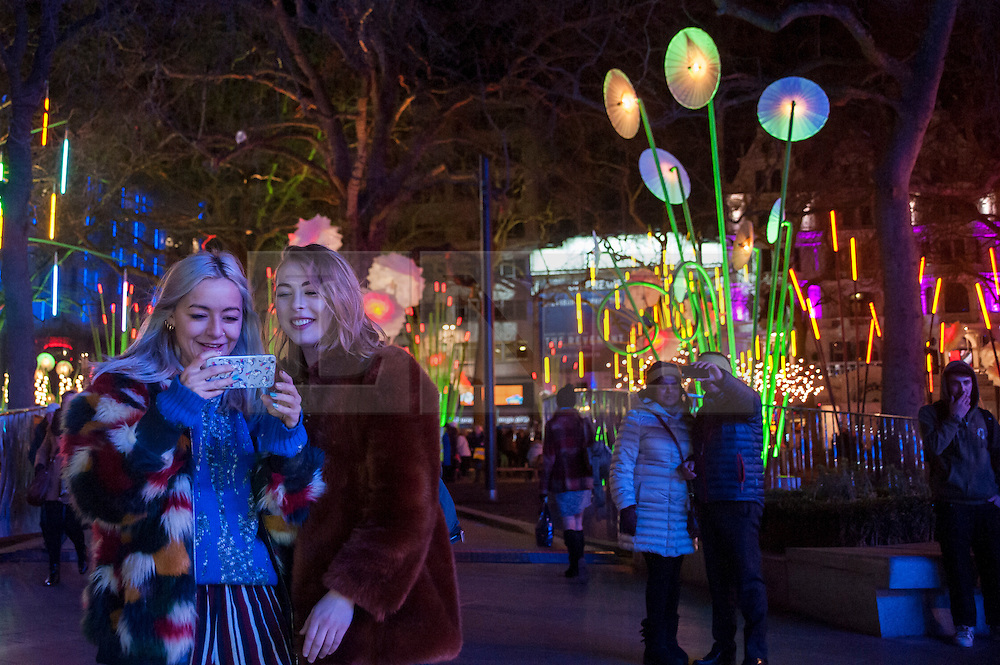 """© Licensed to London News Pictures. 14/01/2016. London, UK. Visitors enjoy """"Garden of Light"""" by TILT in Leicester Square. The work forms part of Lumiere London, a major new light festival which commenced today to be held over four evenings and featuring artists who work with light.  The event is produced by Artichoke and supported by the Mayor of London.  Photo credit : Stephen Chung/LNP"""
