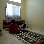 Mohamad Klazly and his mother in a improvised room at a refugee center for Syrian families in Wadi Khaled, Lebanon.