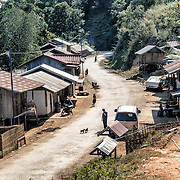 A remote village sits on the side of the road in the rugged terrain of northern Laos.