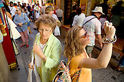 person trying to make a photo in an over crowded street at a tourist destination
