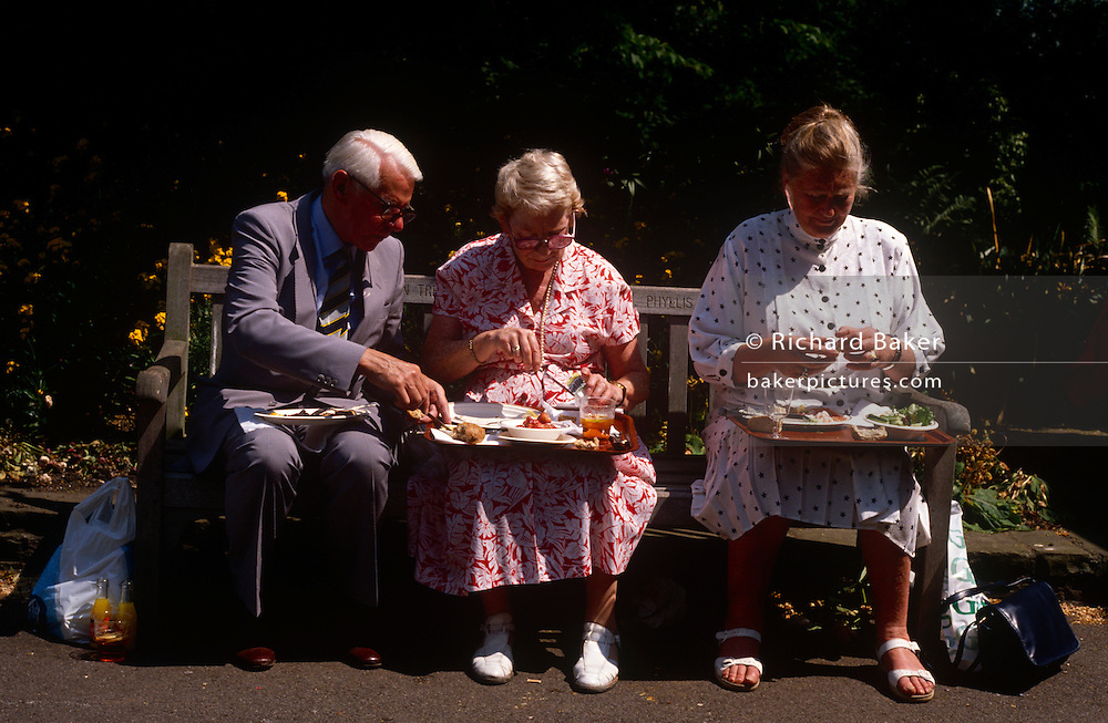 Elderly friends eat lunch on their laps during a mid-day rest at the Chelsea Glower Show. With trays balanced on their knees and sitting on a bench, the man and lady have salads and strawberries and cream and a glass of Pimms - all very English at this most British of annual seasonal summer events.