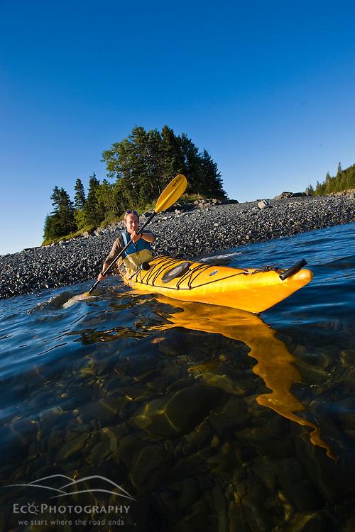 A man sea kayaking near the Porcupine Islands in Maine's Acadia National Park.  Frenchman Bay.  Bar Harbor. Rum Key.