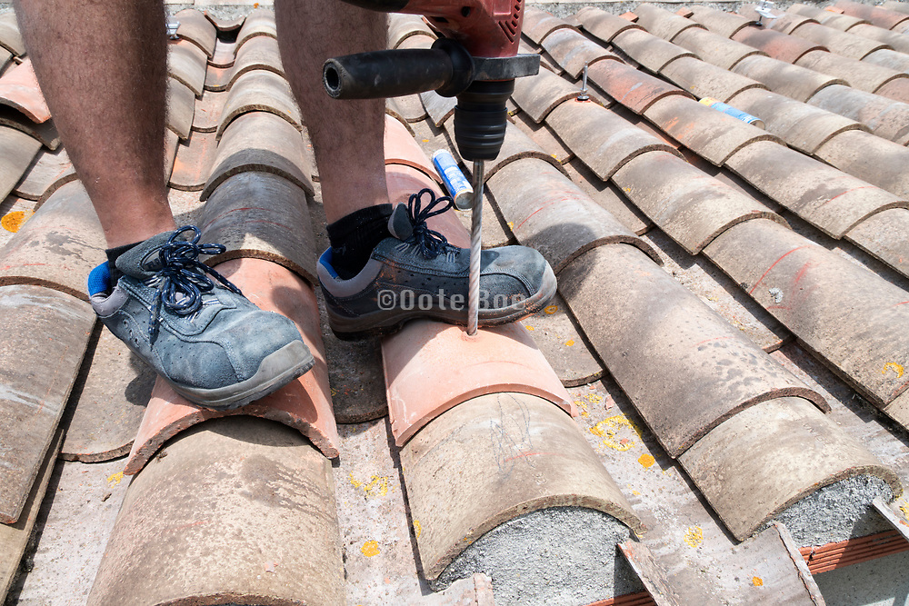 construction worker drilling a hole in a roof tile