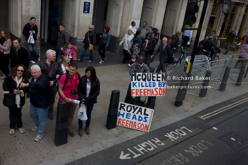 Well-known London Freemasons conspiracy protester stands on Westminster street corner as passers-by walk past.