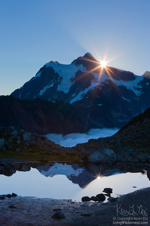 """The sun rises over Mount Shuksan, a 9,127-foot (2,782-meter) peak located in North Cascades National Park, Washington. Shuksan is derived from a Skagit Indian word meaning """"rocky and precipitous."""" The mountain is reflected in a tarn near Artist Point."""