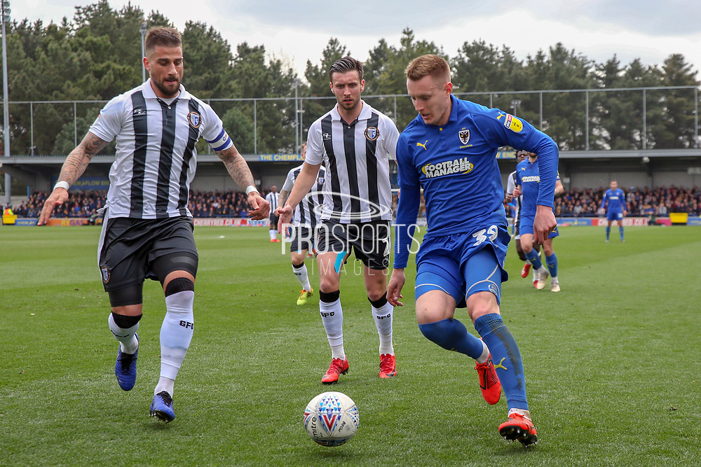 AFC Wimbledon striker Joe Pigott (39) taking on Gillingham defender Max Ehmer (5) during the EFL Sky Bet League 1 match between AFC Wimbledon and Gillingham at the Cherry Red Records Stadium, Kingston, England on 23 March 2019.