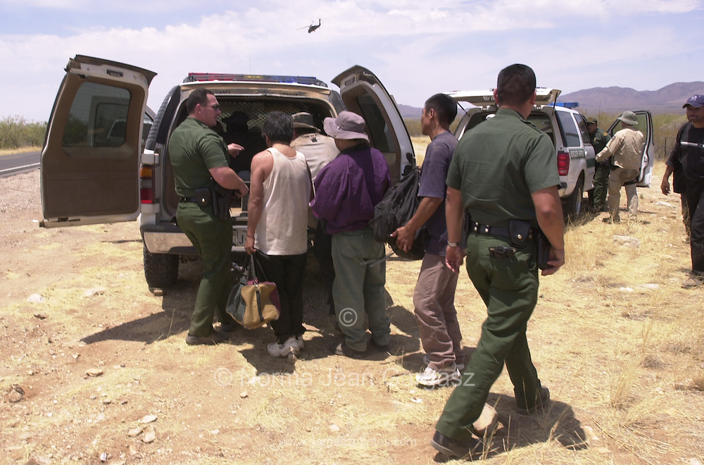 U. S. Border Patrol agents prepare to transport a group of illegal immigrants from Mexico to a shaded area for processing, then a trip to Tucson and deportation.  The group walked for three days in temperatures exceeding 110 degrees before a U. S. Customs helicopter spotted them near milepost 127 north of Route 86 on the Tohono O'odhan Reservation.  The group included a 6-year-old girl who was to be taken by her aunt to New York where the girl's mother lives.  (PHOTO: NORMA JEAN GARGASZ)