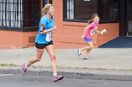 Middletown, New York - A runner gets an escort as she heads for the finish line at the Run 4 Downtown road race on Aug. 18, 2012.