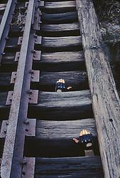 Kid Climbing On Railroad Trestle