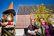Children dressed up for Halloween play at the Statue of Georges Minne underneath the Townhall. Ghent, Belgium, 31.10.2015