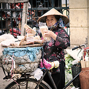 A woman sorts bamboo chopsticks for sale at a morning market in Hanoi, Vietnam.