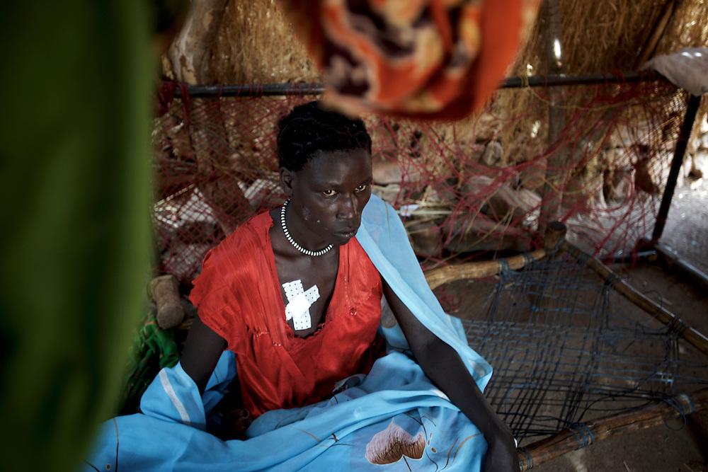 A Nuba woman recovers from shrapnel injuries in a improvised field clinic near Tabania village in South Kordofan's Nuba Mountains in Sudan.