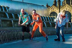Slingshots Top Zombies Alex Noble, Noel Davies-Atack and Paul Byrne outside Sheffield Railway station on Tuesday evening ahead of the game 2.8 Hours Later which reaches the city in August <br /> <br /> 30 June 2015<br />  Image © Paul David Drabble <br />  www.pauldaviddrabble.co.uk