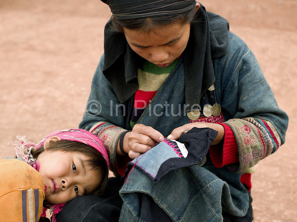 An Akha Nuquie woman sews traditional clothing with her young daughter by her side in Ban Nam Sa village, Phongsaly Province, Lao PDR. One of the most ethnically diverse countries in Southeast Asia, Laos has 49 officially recognised ethnic groups although there are many more self-identified and sub groups. These groups are distinguished by their own customs, beliefs and rituals. These groups are distinguished by their own customs, beliefs and rituals. Details down to the embroidery on a shirt, the colour of the trim and the type of skirt all help signify the wearer's ethnic and clan affiliations.