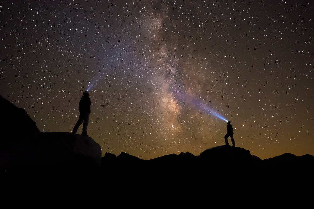 Hikers beneath the Milkyway, headlamps illuminating the night sky, Dusy Basin, Kings Canyon National Forest