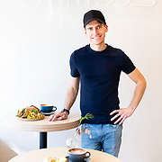 Emmett's Café's managing-partner Josiah Littrell poses for a portrait next to a few signature dishes: a Breakfast Burrito with an Aussie Capp. and a Falafel Pita with roasted vegetables and it's in house made S. High Chai tea. Emmett's Café is located on 744 S. High Street, Columbus Ohio. (photo by Leonardo Carrizo)