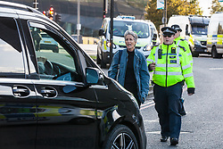 London, UK. 7 September, 2019. A Metropolitan Police officer approaches an activist blocking the road in front of a vehicle outside ExCel London on the sixth day of Stop The Arms Fair protests against DSEI, the world's largest arms fair. The sixth day of protests was billed as a Festival of Resistance and included performances, entertainment for children and workshops as well as activities intended to disrupt deliveries to ExCel London for the arms fair.