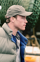 profile of a man wearing a baseball hat and vest outdoors