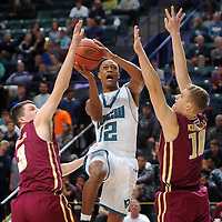 UNCW's C.J. Bryce(12) zips to the net between Elon's Tanner Samson (3) and Karolis Kundrotas (10) in the first half of the game at Trask Coliseum. Mike Spencer/StarNews