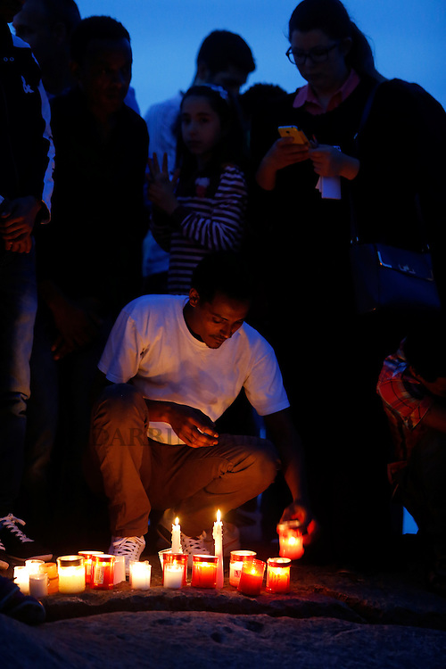 A migrant places candles on the shoreline rocks as they take part in a vigil to commemorate migrants who died at sea in Sliema, outside Valletta, April 22, 2015. European Union leaders who decided last year to halt the rescue of migrants trying to cross the Mediterranean will reverse their decision on Thursday at a summit hastily convened after nearly 2,000 people died at sea.  Public outrage over the deaths peaked this week after up to 900 migrants died last Sunday when their boat sank on its way to Europe from Libya. <br /> REUTERS/Darrin Zammit Lupi MALTA OUT. NO COMMERCIAL OR EDITORIAL SALES IN MALTA
