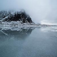 Clouds hide mountain peaks over frozen water of lake Nedreheimredalsvatnet, Eggum, Vestvågøy, Lofoten Islands, Norway