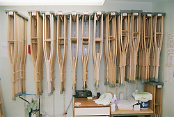 Storage room with rows of crutches suspended on the wall,