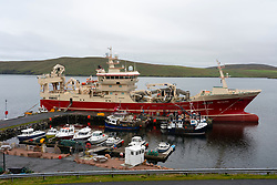 View of small harbour and pier with fishing vessels at Housetter, North Roe, Shetland, Scotland, UK