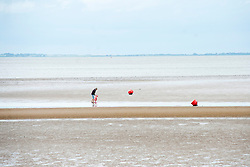 A woman and toddler paddle on Cleethorpes beach. Cleethorpes is situated on    Englands East Coast on the river Humber's tidal estuary. ..1 July 2012.Image © Paul David Drabble
