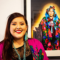 Photographer Hannah Manuelito stands next to the baroque style portrait of her mother at her art opening Saturday evening at Art 123 Gallery in Downtown Gallup.