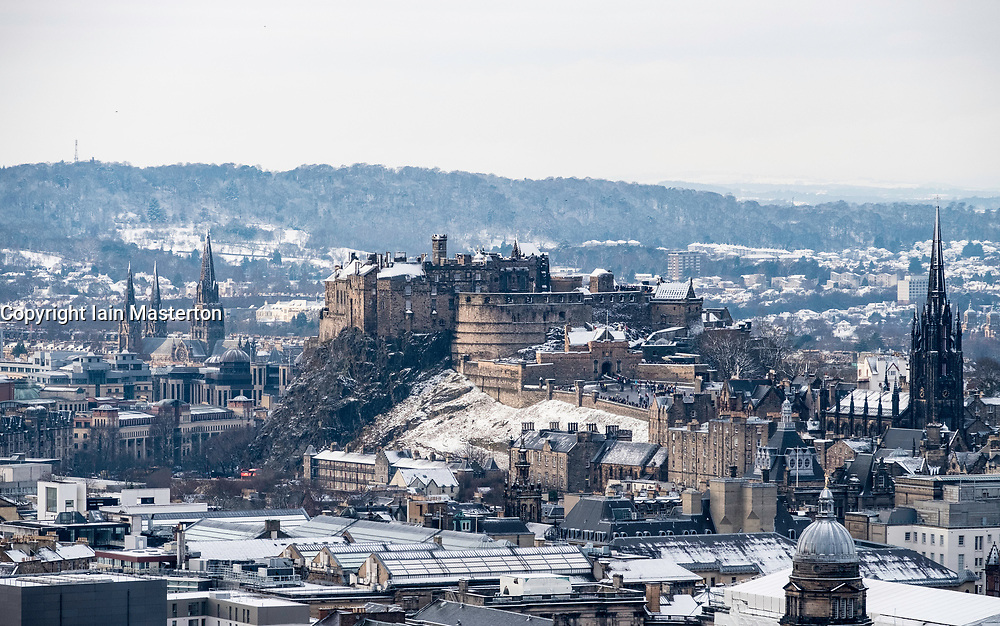 Snow falls on city of Edinburgh in December. Skyline view of city towards the Edinburgh castle from Salisbury Crags ,Scotland, UK.