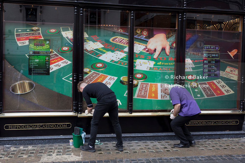 Two men with the Hippodrome Casino polish a brass sill in Leicester Square, on 13th August 2018, in London, England. The Hippodrome Casino has well & truly established itself as a cornerstone of West End life. The biggest & busiest casino in the UK, they are also London's most popular entertainment venue and have welcomed over 7 million visitors since opening in 2012.