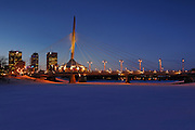 Esplanade Riel Bridge, the Red River and the Winnipeg skyline in winter, dusk, night time<br /> Winnipeg<br /> Manitoba<br /> Canada