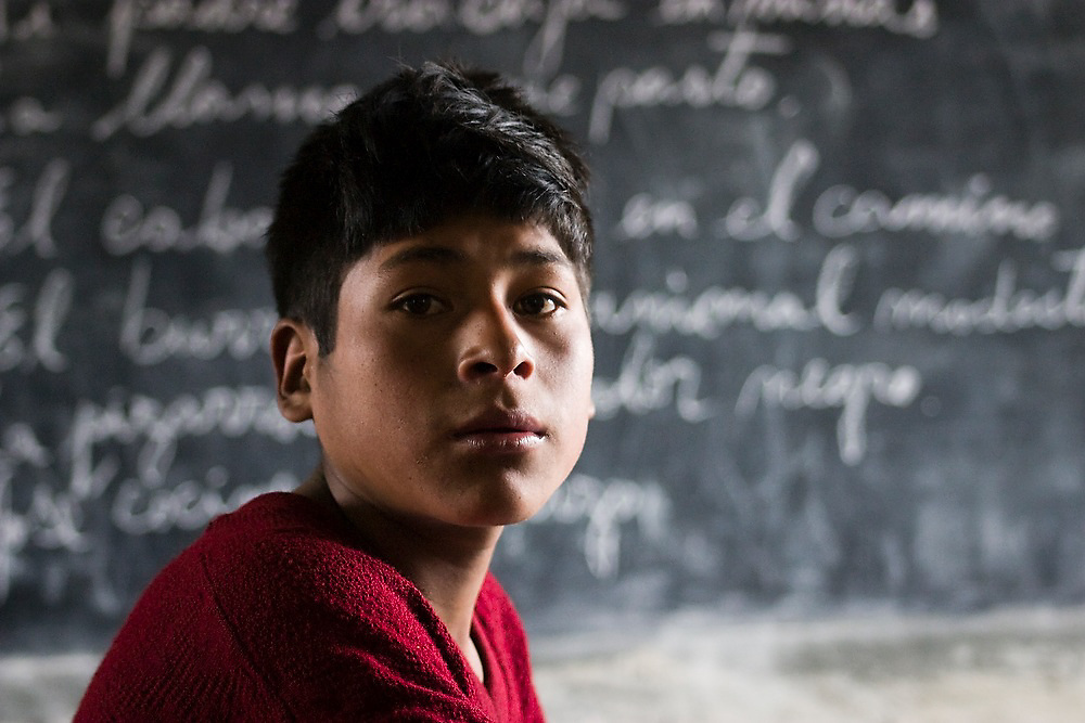 A 5th grade student waits while the teacher attends to the younger students inside the small elementary school in Q'eros, Cordillera de Paucartambo, Andes Mountains, Peru. Spanish sentences are visible on the blackboard behind him. Lessons are taught in both native Quechua and Spanish, the official language of Peru.