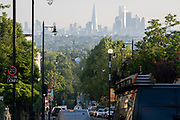 With the London skyline in the far distance, early morning traffic descends the steep 20mph gradient of Gypsy Hill in Crystal Palace, on 16th June 2021, in London, England.