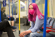 UNITED KINGDOM, London July 14 2020. <br /> Londoner Ramona James matches her face-mask with her hair colour as she travels on the London Underground during a time where masks are mandatory for travelling on public transport due to the COVID-19 pandemic. Ramona, from Enfield, encourages others to bring colour into a time struggle and darkness.