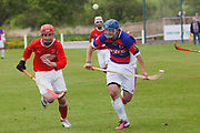 Kingussie (in red and blue) versus Kinlochshiel. An Orion Group Premiership league game.<br /> <br /> Shinty, or 'Camanachd' in Scottish, is a game only played mostly in the Highlands between teams representing villages and towns. The game is older than the recorded history of Scotland and is played on a grass pitch using a small ball and sticks (called a caman). Each team consists of twelve players and the game is played over two halves of 45 minutes. The the aim is to score goals only by using the caman. A ball hit over the sideline results in a 'shy'. To do a shy a player must throw the ball above his or her head and hit the ball with the caman directly over the head using both hands.