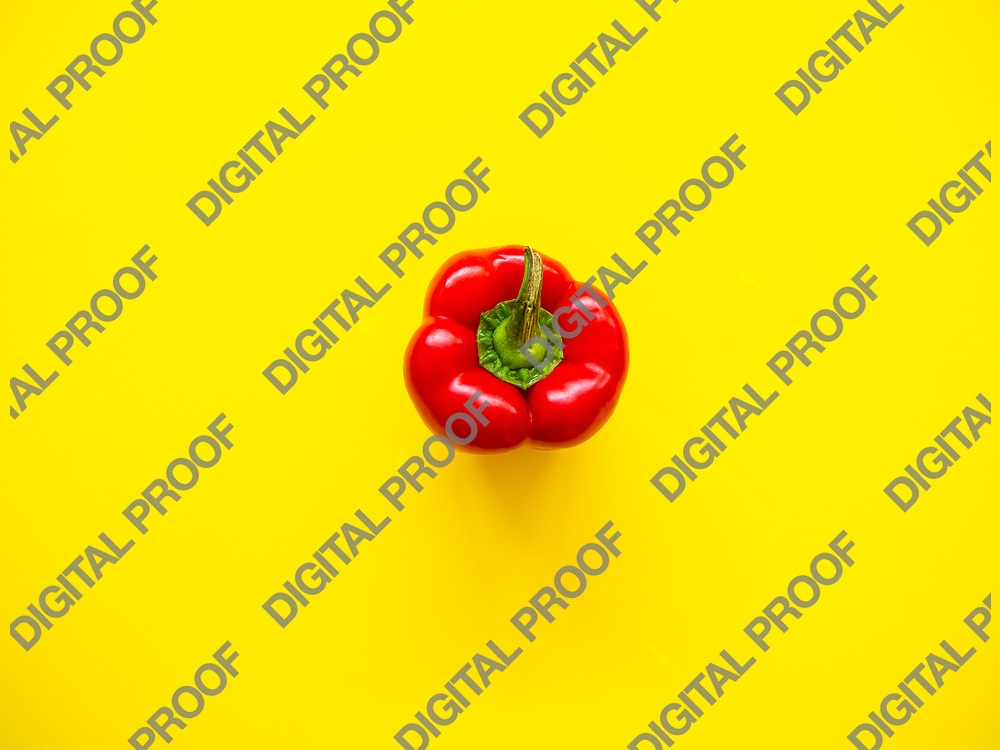 Red bell pepper isolated in studio with yellow background viewed from above as a flatlay concept