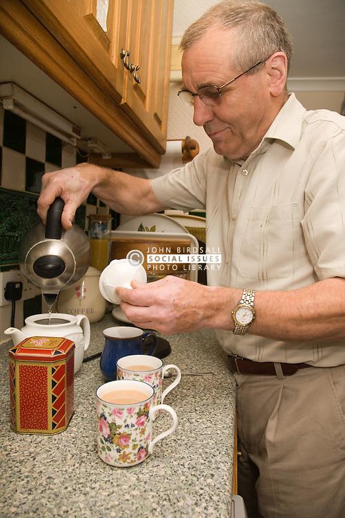 Older man making a pot of tea,