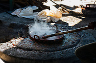 A simmering pot containing the guava-sugar mixture simmers over open flames during the process of making Guyaba bars (Florida, Camagüay Province, Cuba).
