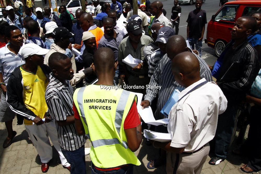 JOHANNESBURG - 31 December 2010 - An immigration assists Zimbabweans at the regional Department of Home Affairs office in Harrison Street on the last day of a deadline for Zimbabweans to apply for residency permits. -- APP/Allied Picture Press