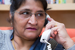 Older woman at home talking on the phone,